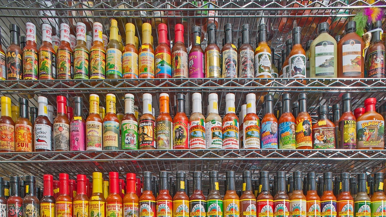 Shelf full of hot sauce bottles